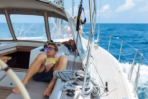 man relaxing on boat with marine board